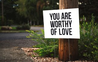 "Picture of sign on telephone that says ""You Are Worthy Of Love"""